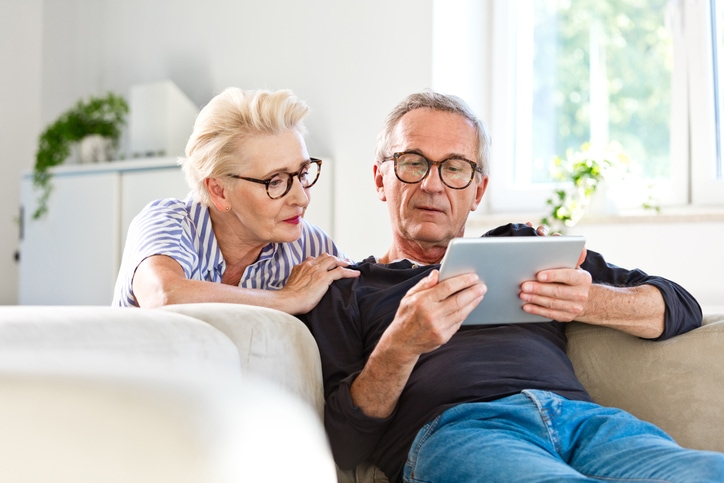 Precision | older couple on couch looking at tablet