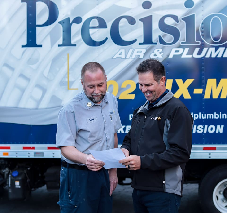 Precision | Two men talking by Precision truck