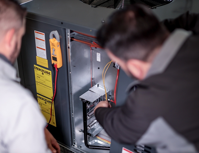Precision   Workers looking at wires on AC unit