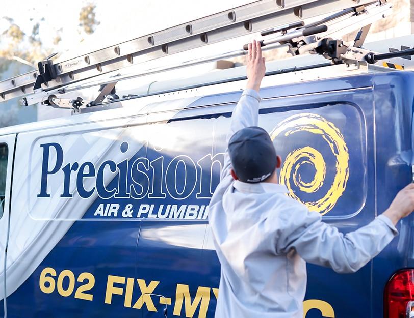 Precision | guy putting a ladder back on vans roof