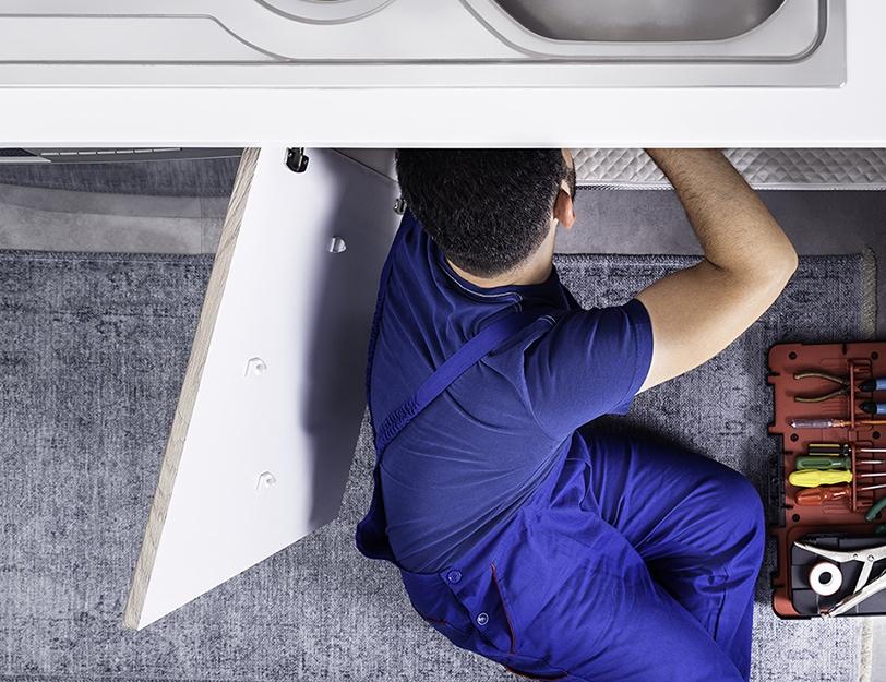 Precision | Plumber working under sink