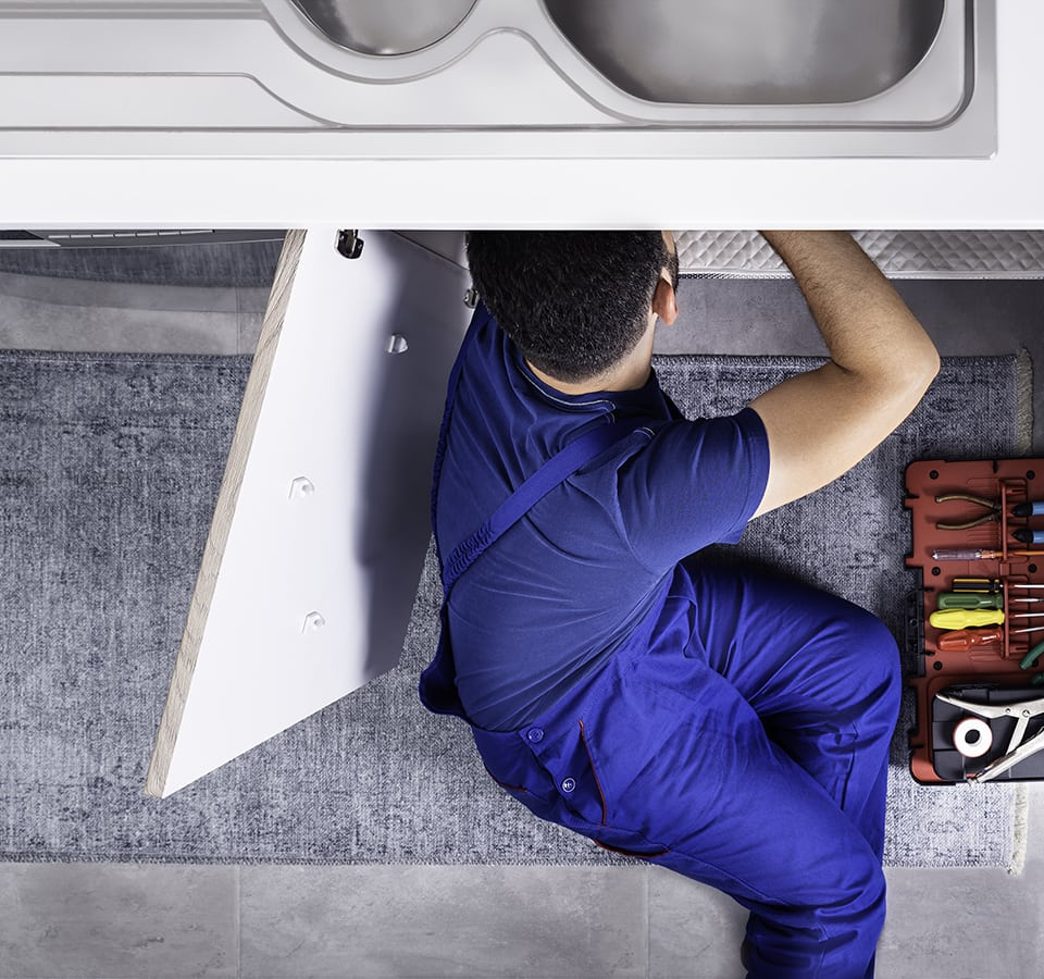 Precision | Plumber working under sink