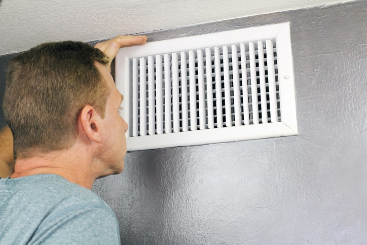 Precision Air & Plumbing | man looking at ac vent