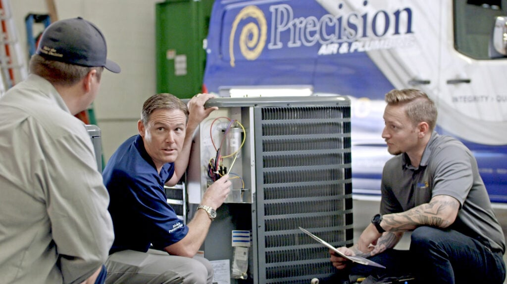 Precision Air & Plumbing | three men looking at ac unit