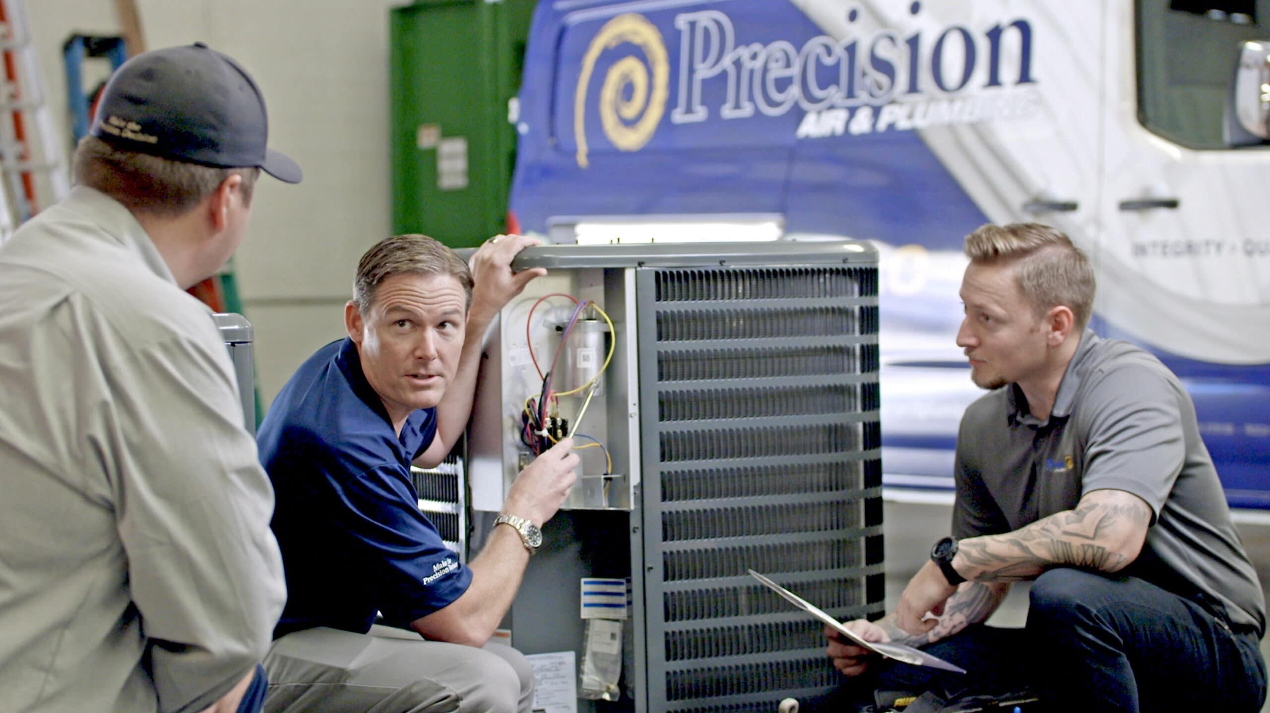 Precision Air & Plumbing   three men looking at ac unit