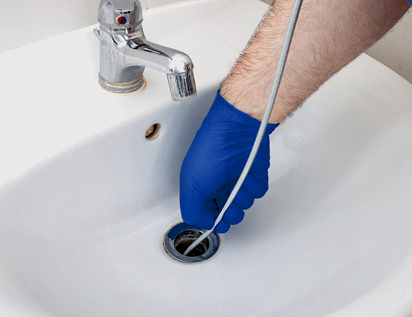 Precision Air & Plumbing | someone unclogging a drain