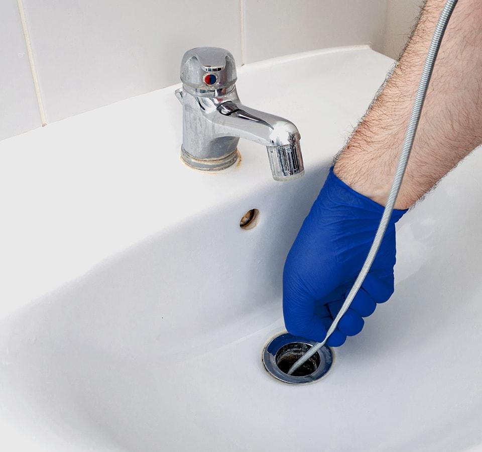 Precision Air & Plumbing   someone unclogging a drain