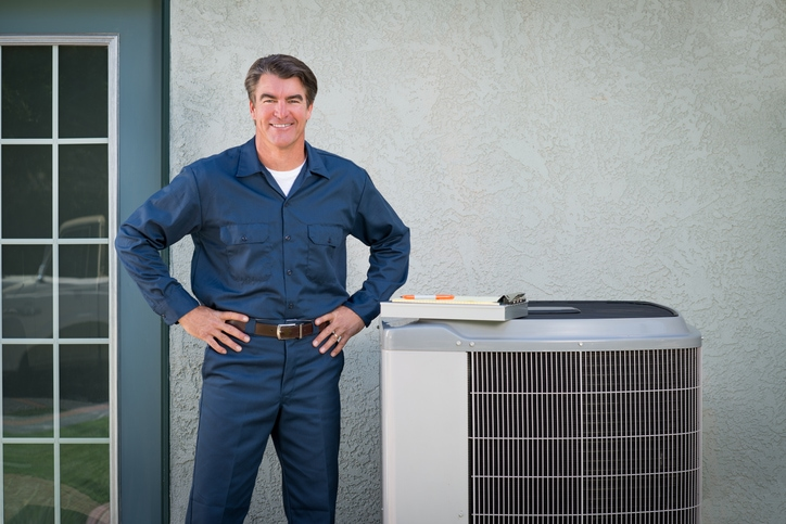 Precision Air & Plumbing | Man standing by an AC Unit
