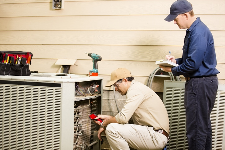 Precision Air & Plumbing | Two men looking at an AC